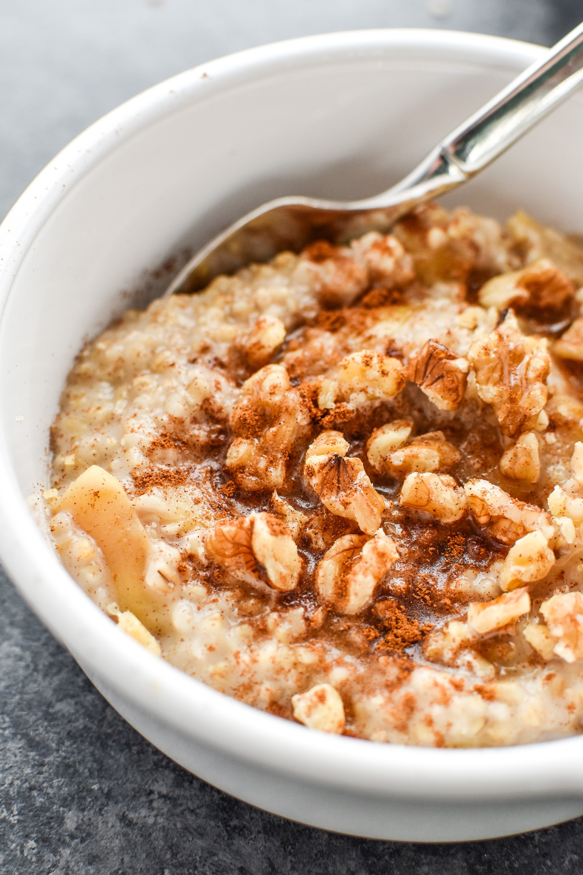 A bowl of cooked steel cut oats with nuts and cinnamon.