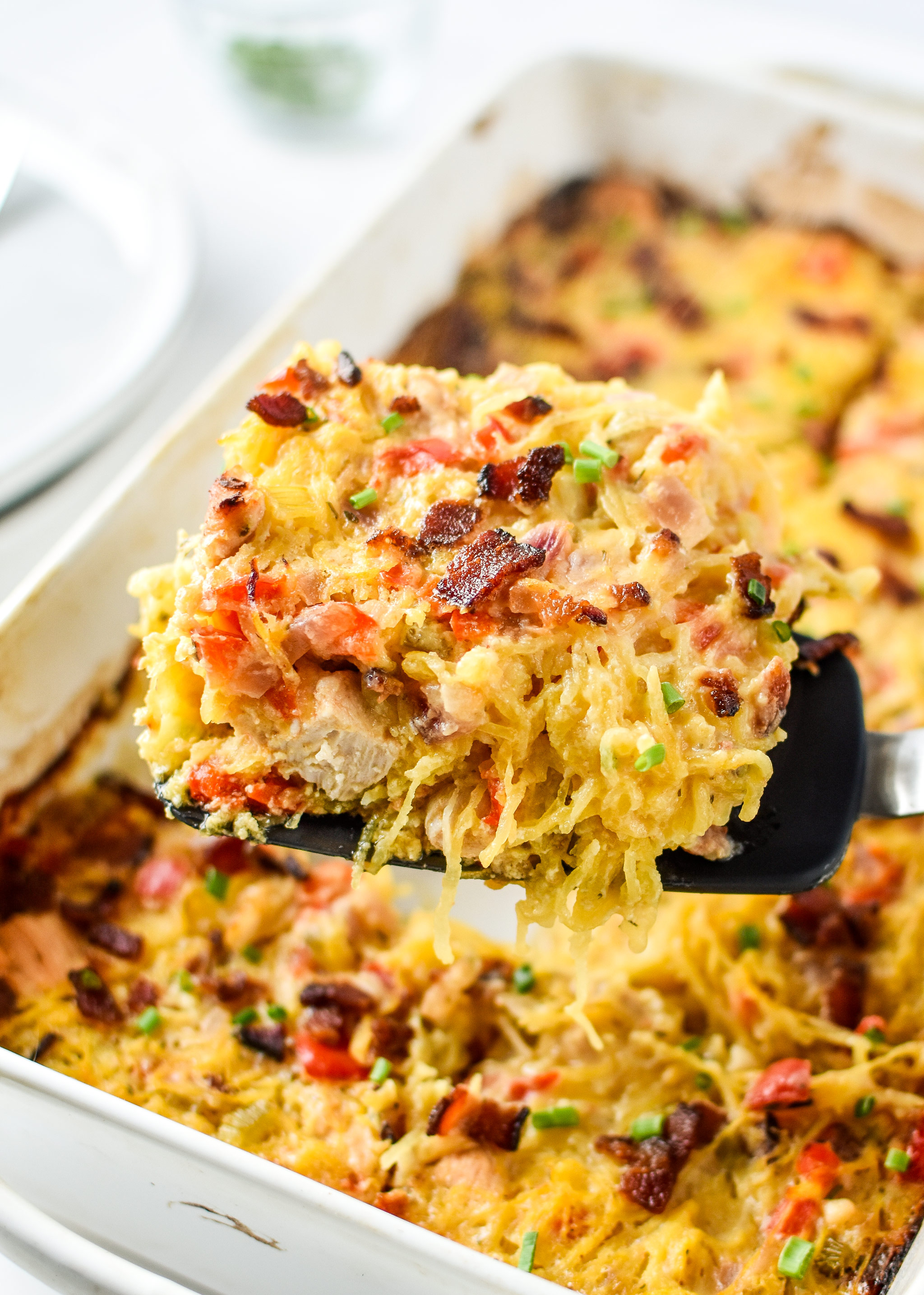 Whole30 Chicken Bacon Ranch casserole being served from a casserole dish.