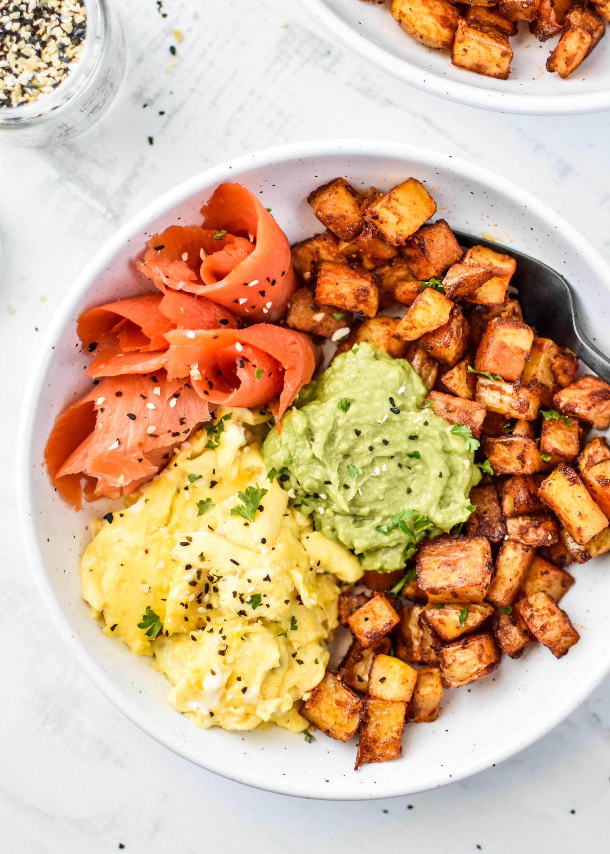 basic oven breakfast potatoes in a bowl with eggs, avocado and smoked salmon