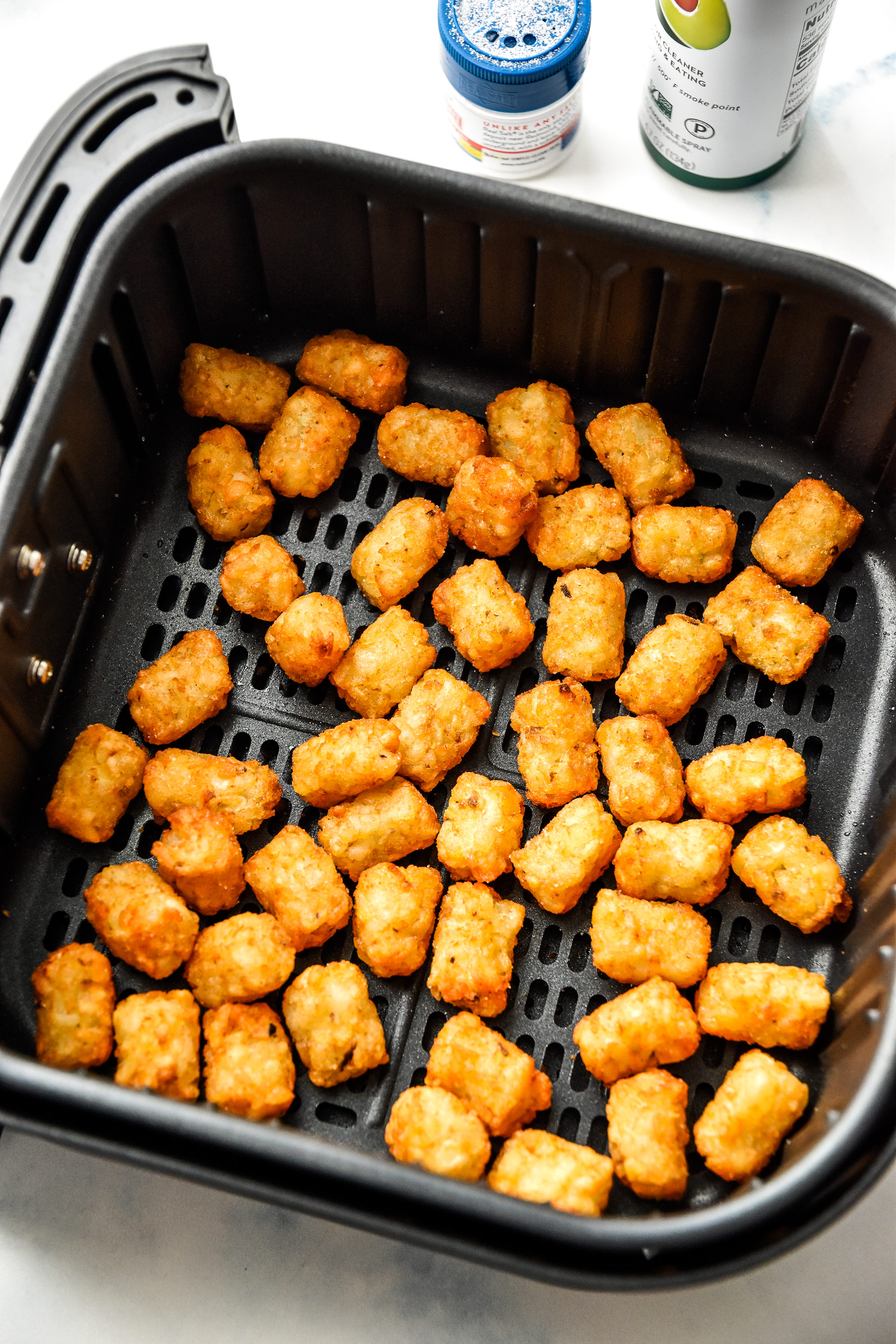 frozen tater tots cooking in an air fryer