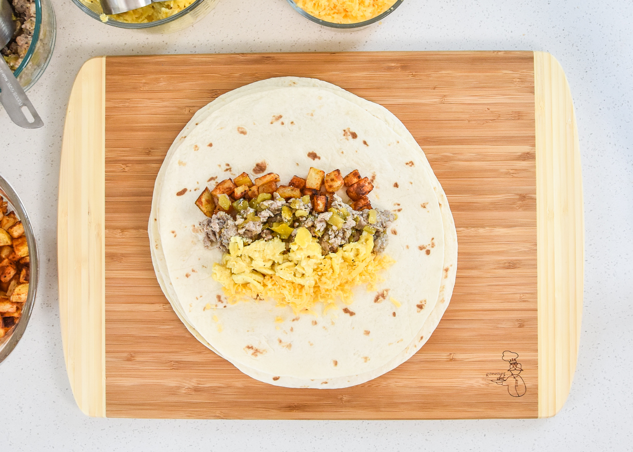 all the ingredients in the air fryer breakfast burritos on a tortilla before being wrapped up