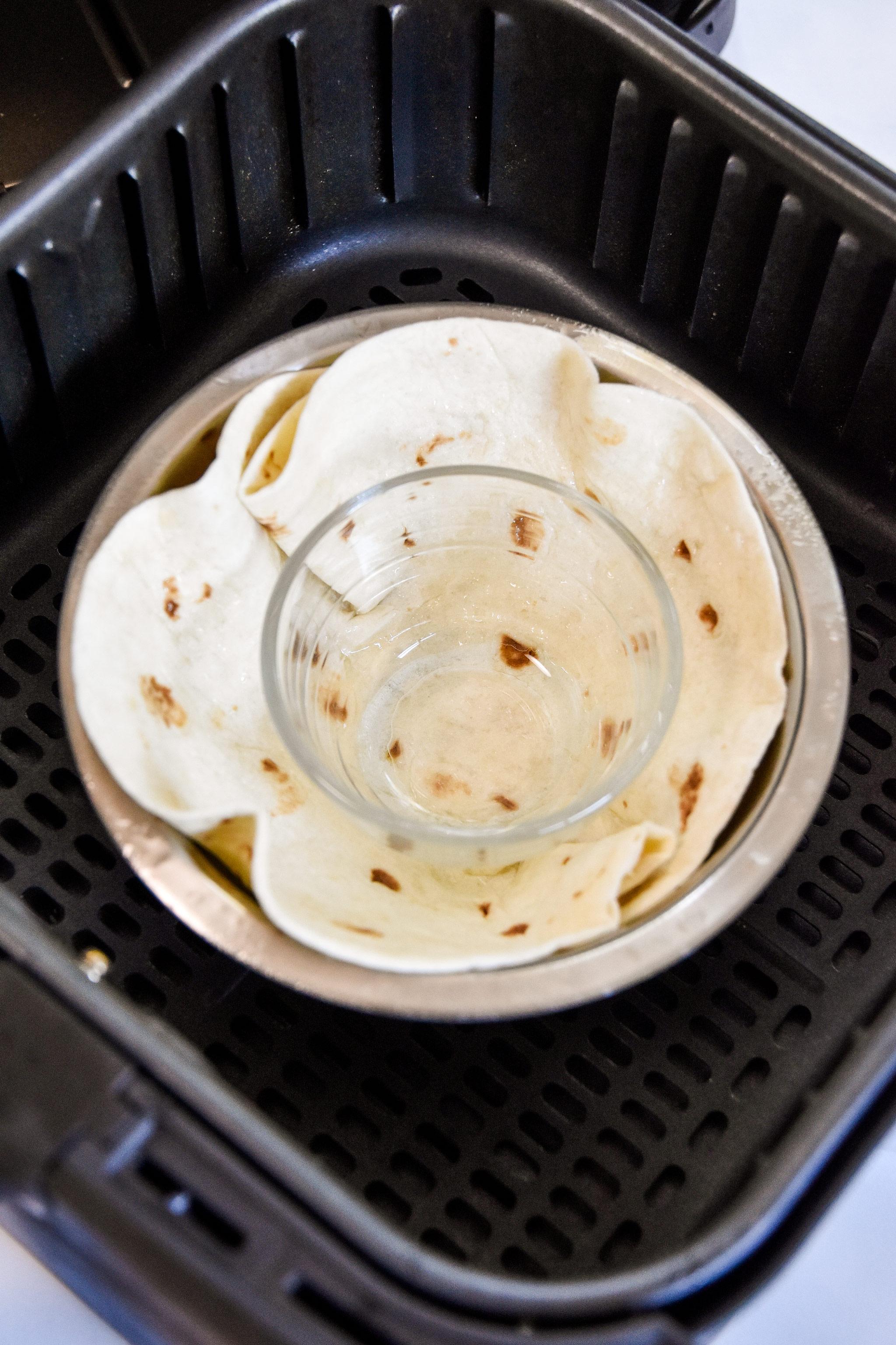 a flour tortilla between two bowls acting as a mold in an air fryer.