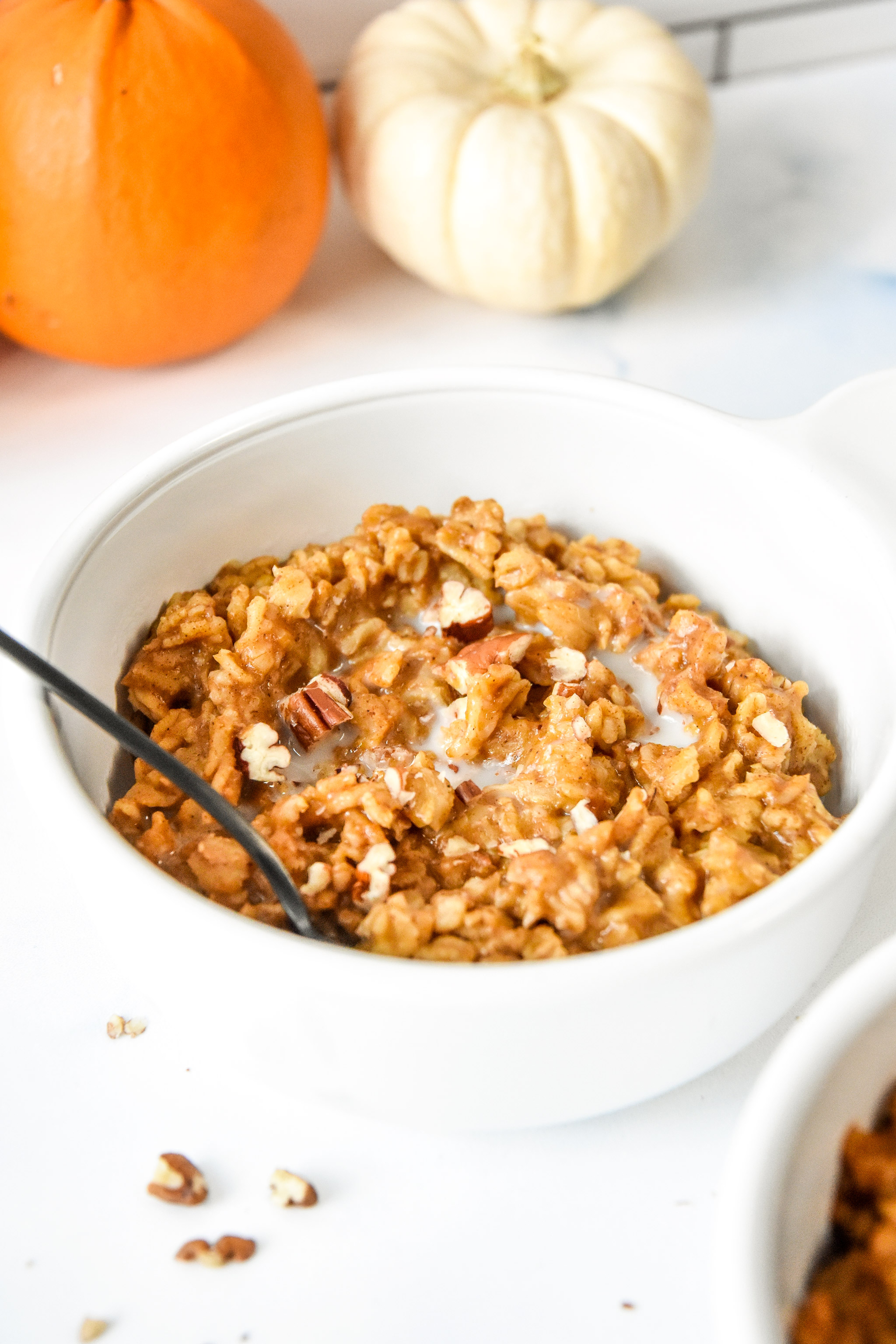 bowl of oatmeal with pecans on top.