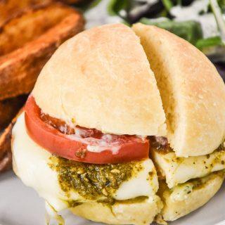pesto chicken mozzarella sandwich with tomatoes on a plate.